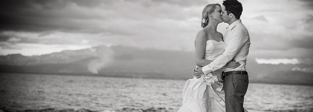 Black and white photo of a bride and groom kissing - Wedding Travel